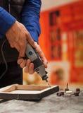 Primer de un hombre del hardworker que perfora un marco de madera con su taladro, con los accesorios de la perforación sobre una  Fotos de archivo