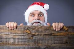 Primer de un hombre divertido con la barba congelada que lleva el casquillo del rojo de santa imagenes de archivo