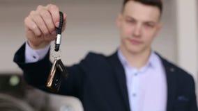 Primer de un hombre en un traje que lleva a cabo las llaves a un nuevo coche en una sala de exposición moderna almacen de metraje de vídeo