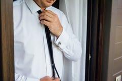 Primer de un hombre en un tux que fija su mancuerna del vintage mancuernas de la corbata de lazo del novio imagen de archivo libre de regalías
