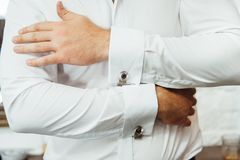 Primer de un hombre en un tux que fija su mancuerna del vintage mancuernas de la corbata de lazo del novio fotos de archivo