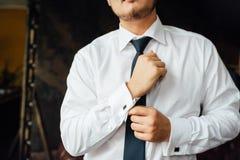 Primer de un hombre en un tux que fija su mancuerna del vintage mancuernas de la corbata de lazo del novio foto de archivo