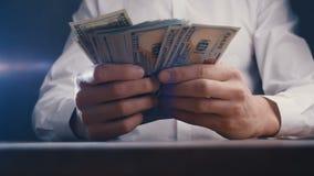 Primer de un hombre de negocios enojado que cuenta el dinero y que bate su puño en la tabla Engaño con el pago almacen de video