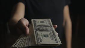 Primer de un hombre que da un barril de billetes de dólar El concepto de salarios caridad almacen de video
