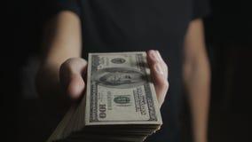 Primer de un hombre que da un barril de billetes de dólar El concepto de salarios caridad almacen de metraje de vídeo