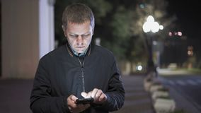 Primer de un hombre que hojea a través de contactos en Smartphone que coloca en medio de la noche la ciudad almacen de video
