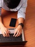 Primer de un hombre que pone mecanografiar en el Smart-reloj y el móvil que llevan del ordenador portátil por otra parte imagen de archivo libre de regalías