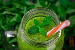 Primer de un jugo del kiwi Vista superior de un tarro de albañil del smoothie verde en un fondo de las hojas Concepto de la salud imágenes de archivo libres de regalías