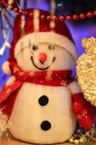 Primer de un muñeco de nieve del juguete del blanco puro con malla de la Navidad en el fondo foto de archivo libre de regalías