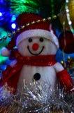 Primer de un muñeco de nieve del juguete del blanco puro con malla de la Navidad en el fondo fotografía de archivo libre de regalías