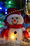 Primer de un muñeco de nieve del juguete del blanco puro con malla de la Navidad en el fondo fotos de archivo libres de regalías
