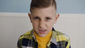 Primer de un muchacho lindo encantador que mira la cámara él enojado y hecho muecas su cara 7 - 8 años enojados hermosos de mucha metrajes