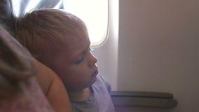 Primer de un niño pequeño que duerme en un aeroplano que se inclina en el hombro de su madre metrajes