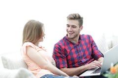 Primer de un par joven sonriente con el ordenador portátil Fotos de archivo