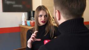 Primer de un par que se sienta en una cafetería con las tazas de café blancas almacen de metraje de vídeo