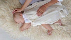 Primer de un pequeño muchacho recién nacido que duerme en una manta en casa en el dormitorio almacen de metraje de vídeo