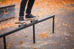 Primer de un pie del ` s del skater en un parque del patín del otoño Imagen de archivo