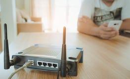 Primer de un router inalámbrico y de un hombre joven que usa un smartphone en sala de estar en casa con una ventana en el fondo imagen de archivo libre de regalías