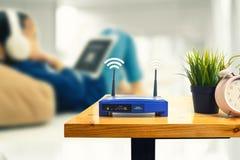 Primer de un router inalámbrico y de un hombre que usa smartphone en ofiice de la sala de estar en casa imagen de archivo