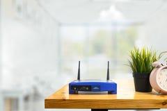 Primer de un router inalámbrico y de un hombre que usa smartphone en ofiice de la sala de estar en casa fotografía de archivo