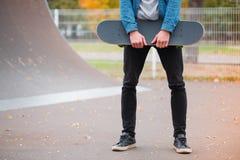 Primer de un skater que sostiene un monopatín en manos Imagen de archivo libre de regalías