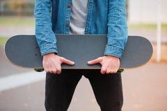 Primer de un skater que sostiene un monopatín en manos Fotos de archivo libres de regalías