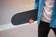 Primer de un skater que sostiene un monopatín en manos Imagenes de archivo