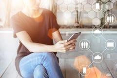 Primer de un smartphone en manos femeninas En primero plano son los iconos virtuales con las nubes, gente, artilugios digitales Imagen de archivo libre de regalías