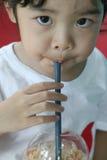Primer de un té de la leche de consumo de la niña Imagen de archivo libre de regalías