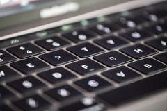 Primer de un teclado detrás iluminado con una profundidad muy baja de la opinión sobre las llaves centrales imagen de archivo libre de regalías