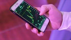 Primer de un teléfono móvil de Analyzing Graph On del hombre de negocios existencias Primer del gráfico de Person Hand Using Cell fotografía de archivo