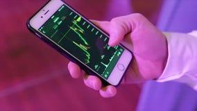 Primer de un teléfono móvil de Analyzing Graph On del hombre de negocios existencias Primer del gráfico de Person Hand Using Cell metrajes
