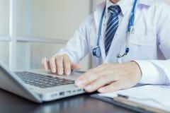 Primer de un trabajador médico que mecanografía en el ordenador portátil foto de archivo