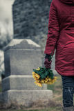 Primer de un triste delante de una lápida mortuaria Foto de archivo