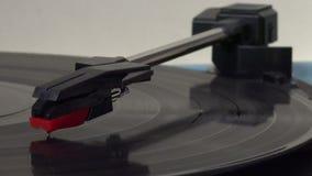 Primer de una aguja en un disco de vinilo que juega en un estéreo metrajes