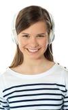 Primer de una belleza sonriente que disfruta de música Fotografía de archivo libre de regalías