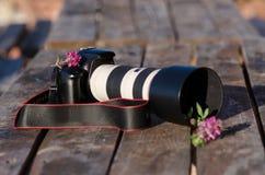 Primer de una cámara del dslr rodeada por las flores fotos de archivo libres de regalías
