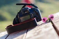 Primer de una cámara del dslr rodeada por las flores Foto de archivo libre de regalías