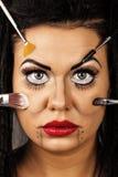 Primer de una cara de la mujer joven usando los cepillos para las mejoras Fotografía de archivo libre de regalías