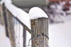 Primer de una cerca de madera vieja cubierta con la nieve, fondo borroso Foto de archivo