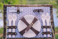 Primer de una cesta de la maleta de la comida campestre con los platos - placas, cucharas y bifurcaciones imágenes de archivo libres de regalías