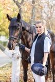 Primer de una chica joven, con un caballo en el parque para un paseo, en la mano de un casco Fotos de archivo libres de regalías