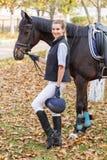 Primer de una chica joven, con un caballo en el parque para un paseo, en la mano de un casco Fotografía de archivo