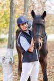 Primer de una chica joven, con un caballo en el parque en un paseo que mira la cámara, sonriendo Imágenes de archivo libres de regalías
