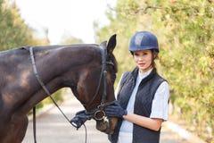 Primer de una chica joven, con un caballo en el parque que mira la cámara, sonriendo Imagenes de archivo