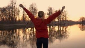 Primer de una chica joven que hace la situación de la gimnasia en la puesta del sol en un parque de la ciudad Ella entrena en el  almacen de metraje de vídeo