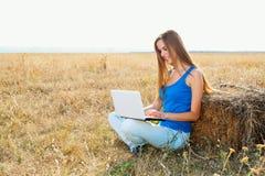 Primer de una chica joven que usa la computadora portátil Fotografía de archivo