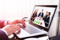 Primer de una comunicación video de la mano del ` s del empresario en el ordenador portátil fotos de archivo