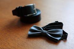 Primer de una corbata de lazo que miente en una tabla, vistiendo al novio Imagen de archivo libre de regalías