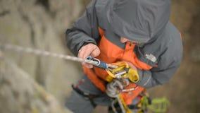 Primer de una ejecución del escalador de roca en una cuerda y las carabinas y el seguro el desenredar almacen de video